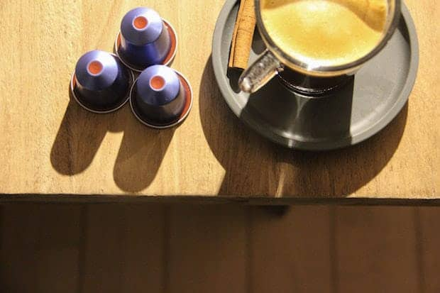 Nespresso coffee and three coffee capsules at the edge of a table