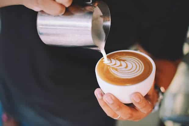Barista topping a cappuccino or latte with foamed milk