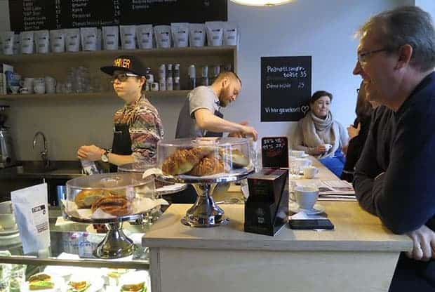 Customers and baristas banter over the counter of an Oslo coffee shop