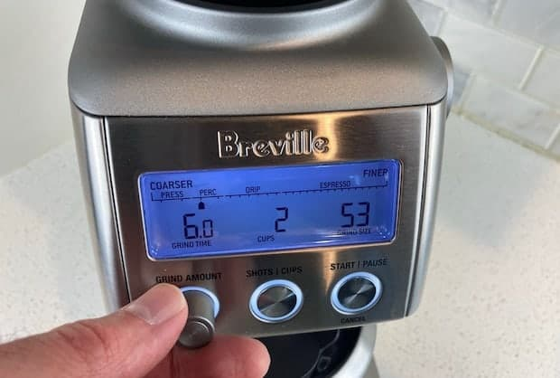 Closeup of the Breville Smart Grinder Pro with a hand on the grind time knob