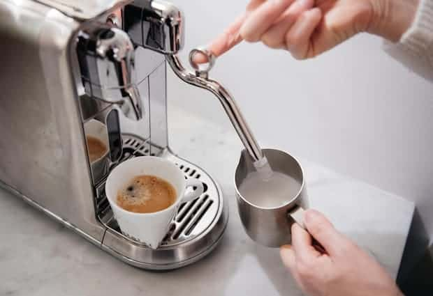 A pair of hands frothing milk with a Nespresso Creatista Plus