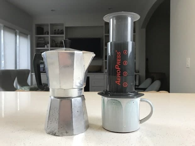 A moka pot and an AeroPress standing side-by-side on a kitchen counter