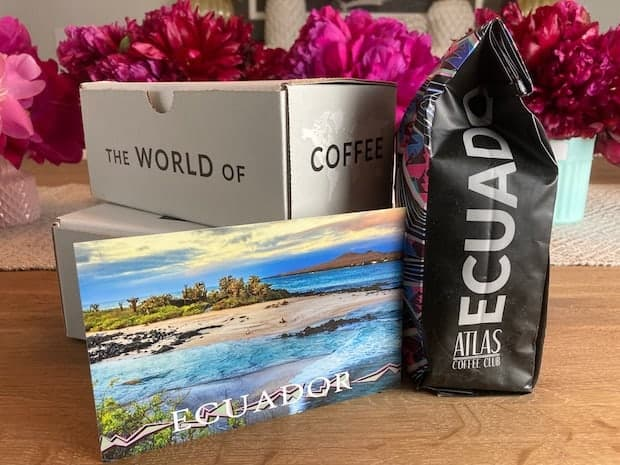 Bag of coffee from Ecuador on a table with a postcard and some flowers