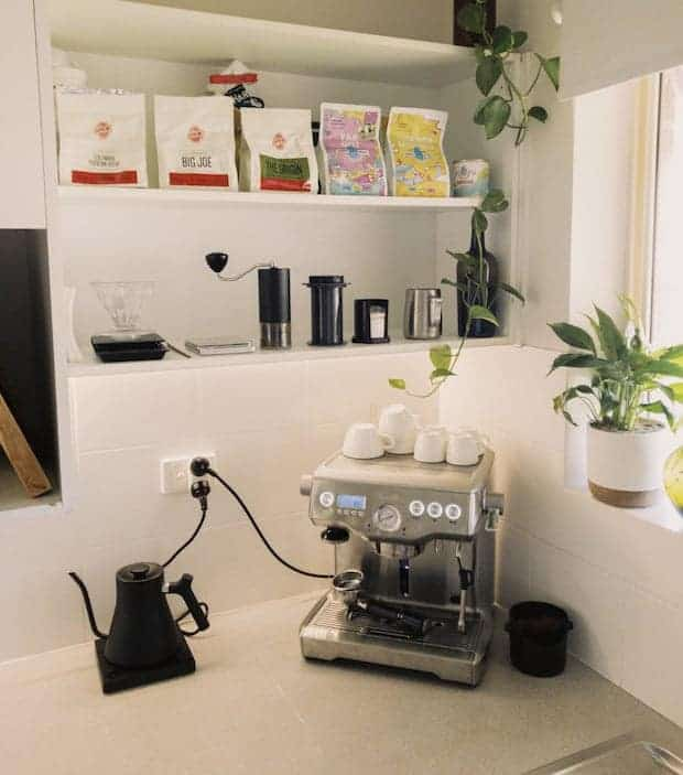 Coffee station on a kitchen counter with shelves above