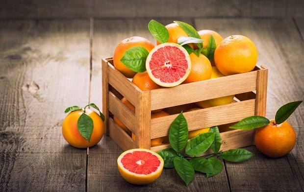 грейпфруты в деревянном ящике с листьями