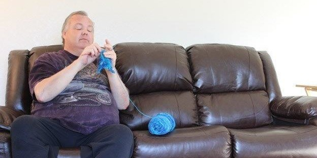 man crocheting on couch