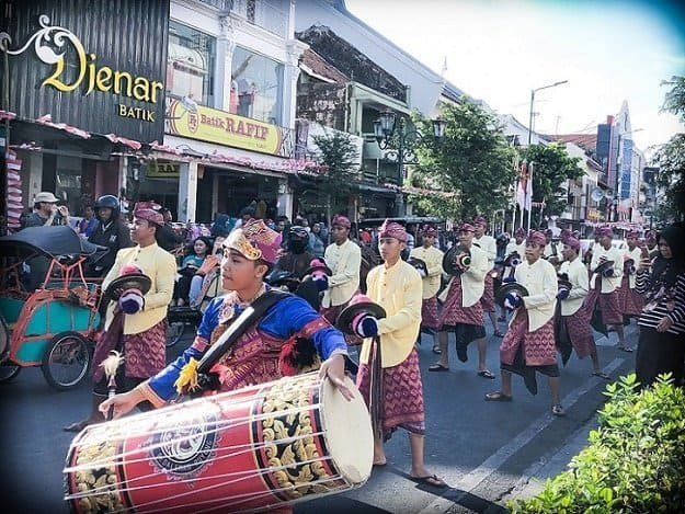 A musical group dressed in traditional Indonesian clothing perform on the street in Yogyakarta, where people can learn Indonesian. A drummer leads the procession, along with men in cymbals.