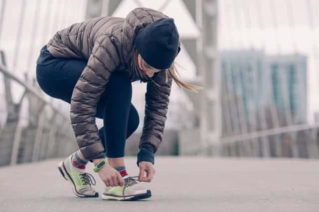 woman tying her shoe before a run