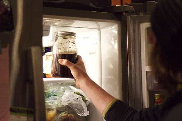 A hand pulling a jar of cold brew coffee concentrate ot of a refrigerator
