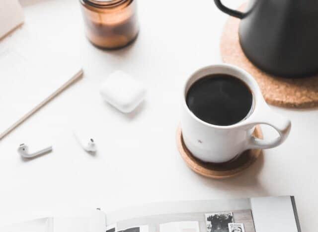 テーブルの上にあるイヤホンとコーヒー