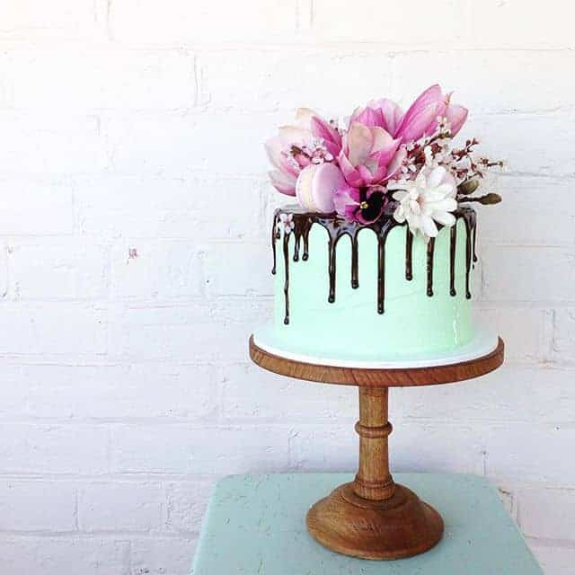 Chocolate Cake with green icing and chocolate drizzle topped with magnolias! By Mudgee Made