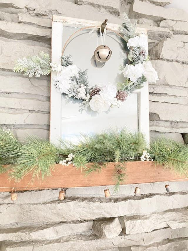 an old window turned into a mirror with a hoop wreath and an old gold bell hanging from it, a spruce garland with white berries mixed in, and an antique bell garland.