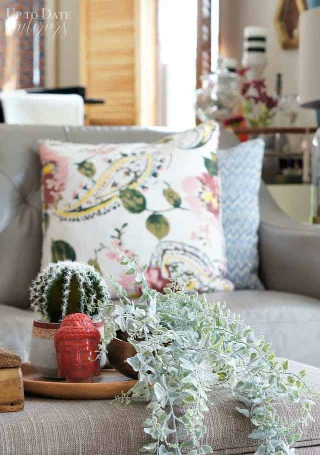 how to bring spring into your home with global elements and a plant on a coffee table upholstered bench with floral and blue pillows on the sofa