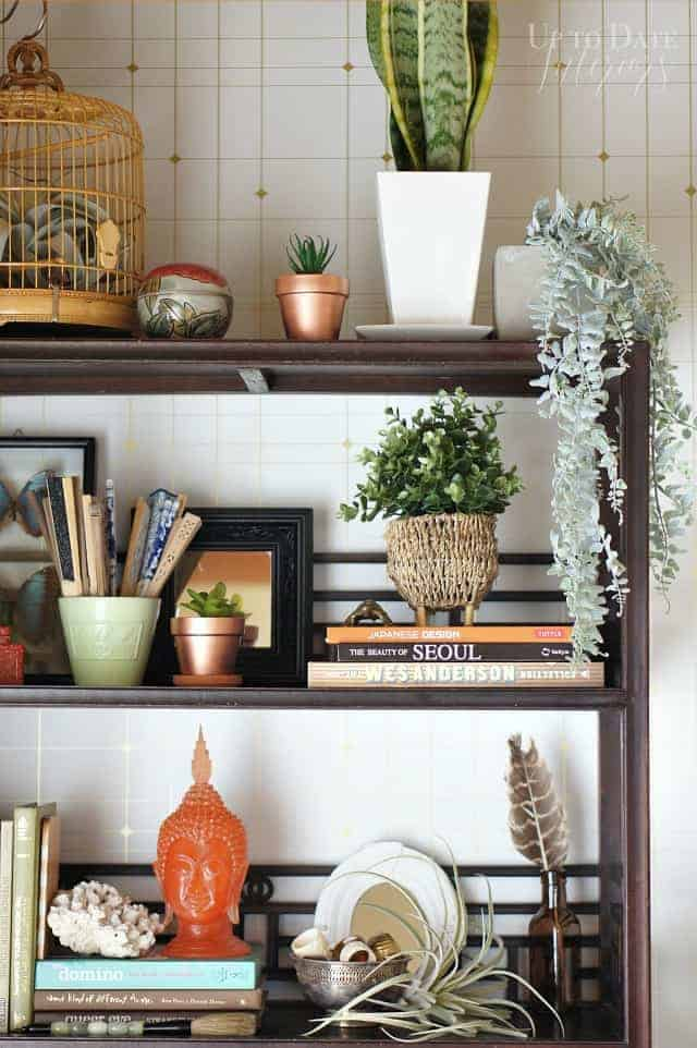 bookcase styled with plants, copper, green, and pops of orange