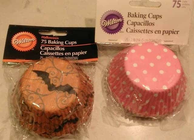 Cupcake liners with designs on the outside: on the left, an orange Halloween liner with a black bat, and on the right, a pink liner with white polka-dots.