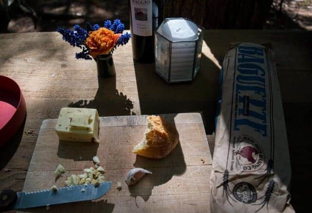 a picnic spread, including bread, cheese, and fresh flowers.