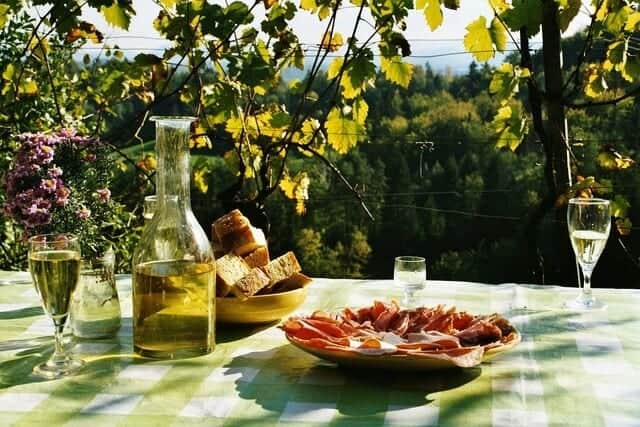 a picnic table with a plate of meats and a carafe of wine.