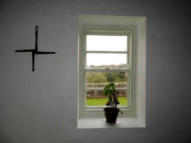 A St Brigid's Cross hanging on a white wall in an Irish home with a small window next to it.
