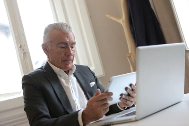 man in black suit looking at computer