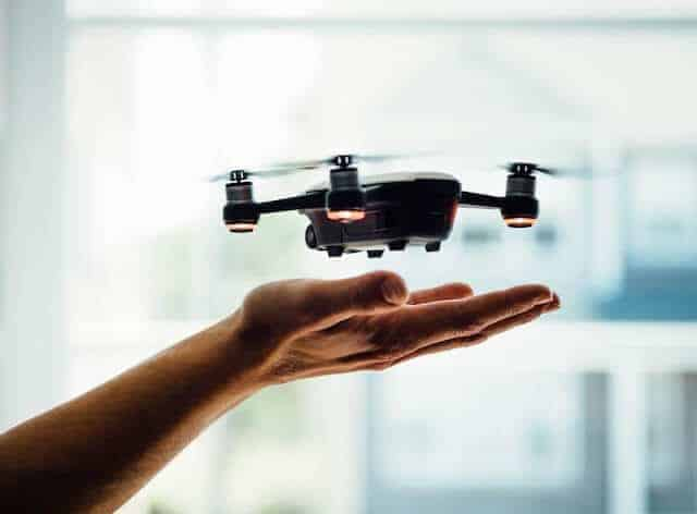 Top 10 Drone Accessories - Hand underneath a switched on drone