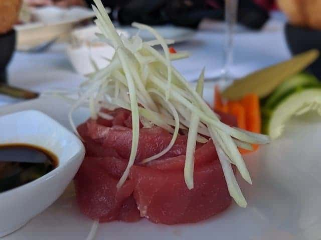 Tuna Sashimi in focus next to soy sauce and wasabi in the background