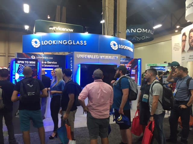 Trade show attendees line up to play Virtual Prize Wheel game