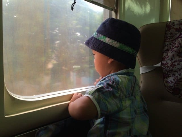 A kid riding the train in Indonesia, traveling internationally with kids