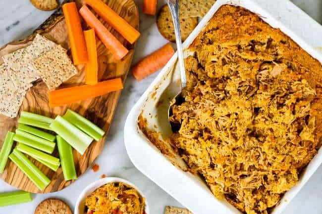 Healthy buffalo chicken dip in baking dish with spoon, crackers, carrots and celery.