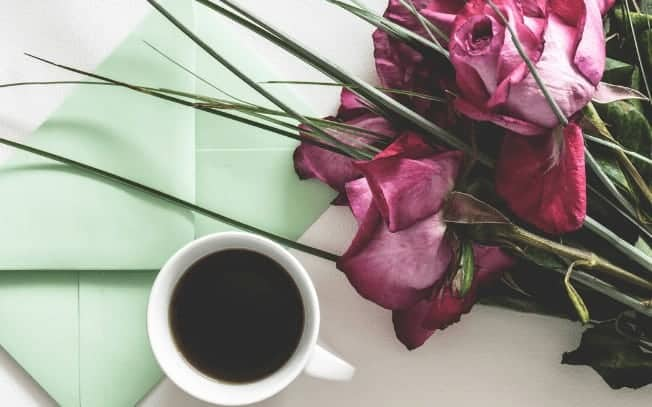 flowers beside a cup of coffee and green envelope