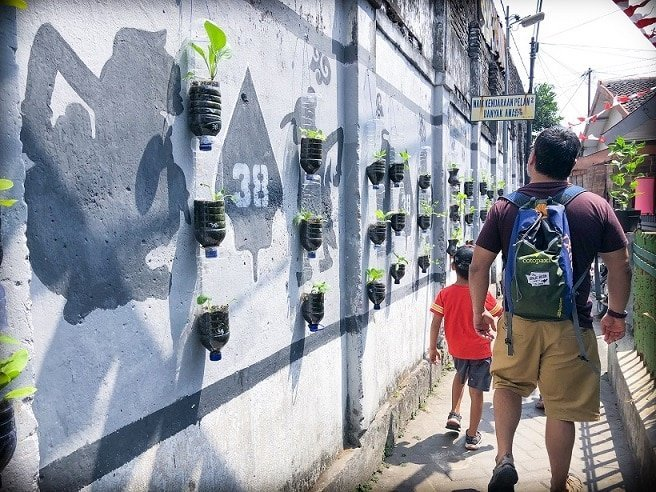 A man and a young boy walk through a small walkway in Yogyakarta, Indonesia, where travelers can learn Indonesian. To the left of them, they pass a wall decorated with plastic bottles that have been converted into planters, and paintings of shadow puppets on the wall.
