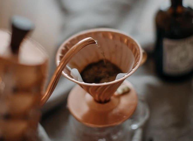 A copper Hario gooseneck kettle pouring into a copper Hario V60 brewer