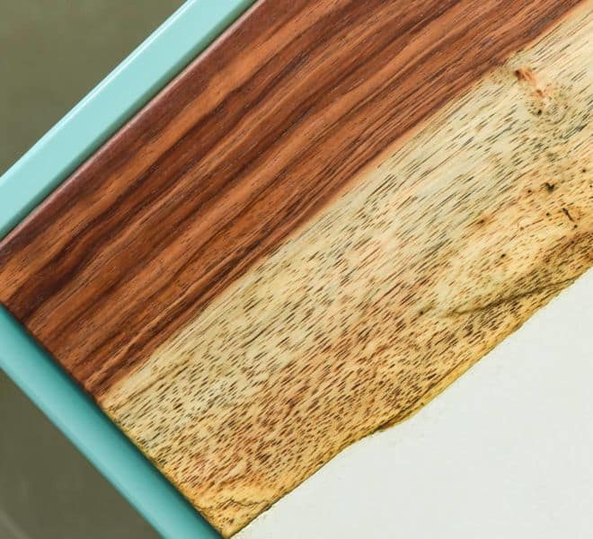 Close Up Image of a Concrete and Guanacaste End Table on a Teal Powder Coated Steel Base