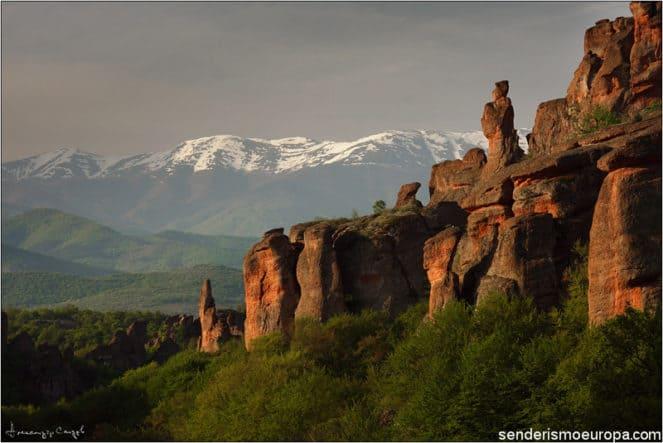 Rocas ferricas de Belogradchik con fondo nevado