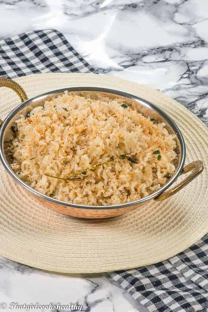 Toasted coconut caribbean rice in a bowl with herbs