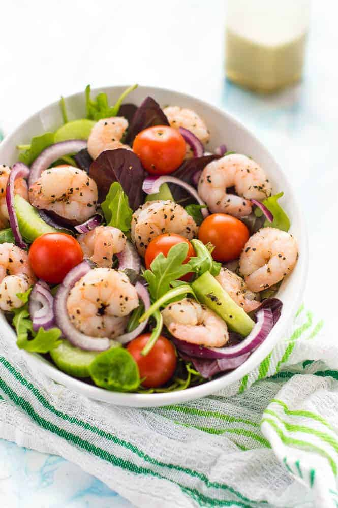White bowl with shrimp, rocket and tomatoes