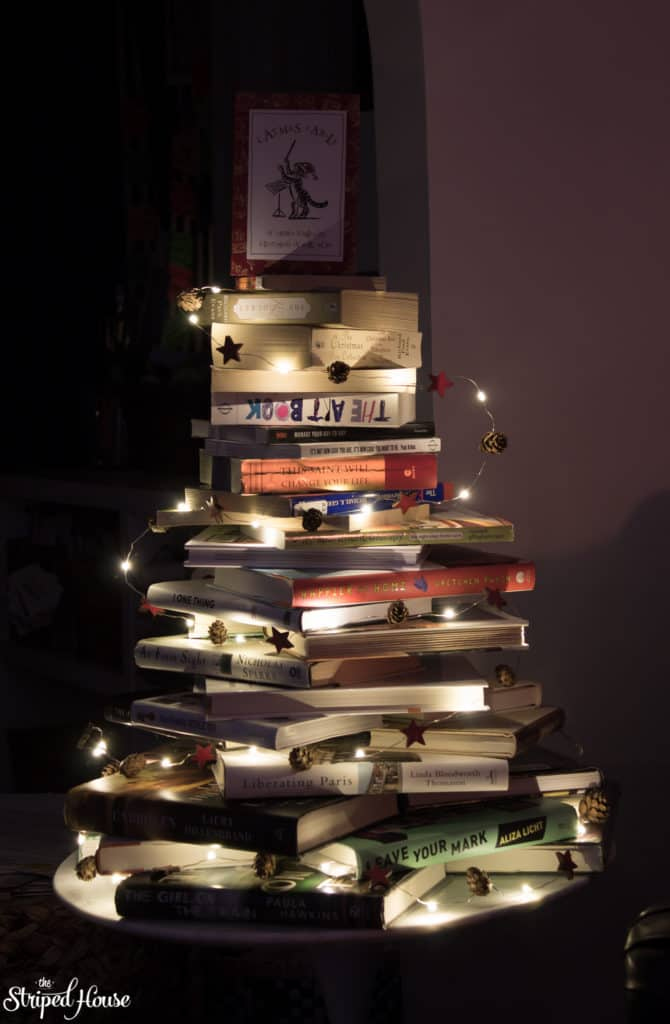 Books stacked in the shape of a Christmas tree with lights wrapped around it.  Classic simple Christmas decorations in my home.