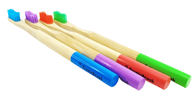 TropicBrush Bamboo Toothbrushes. Image shows 4 toothbrushes lined up. There's a blue, purple, red and green toothbrush.