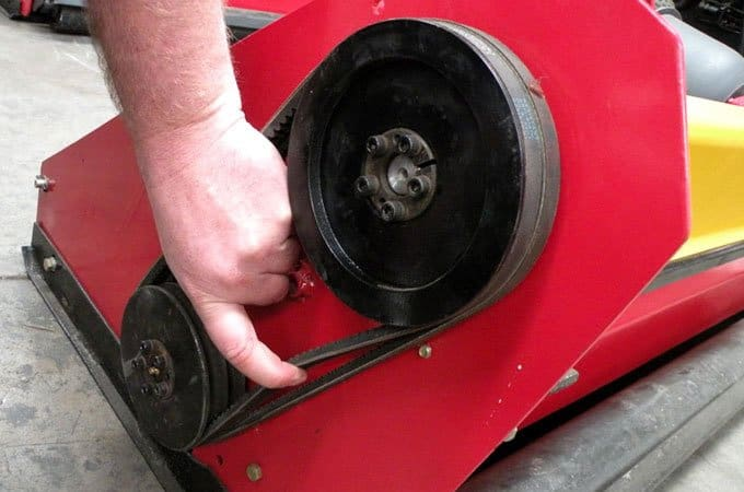 Check for tension by pulling the belt at it's midpoint between the pulleys. The tension on this flail mower belt is too loose.