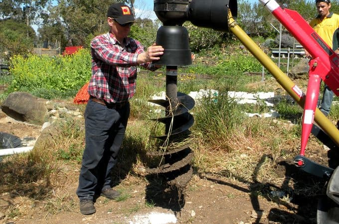 An offsider guides the auger to a place marked for digging.