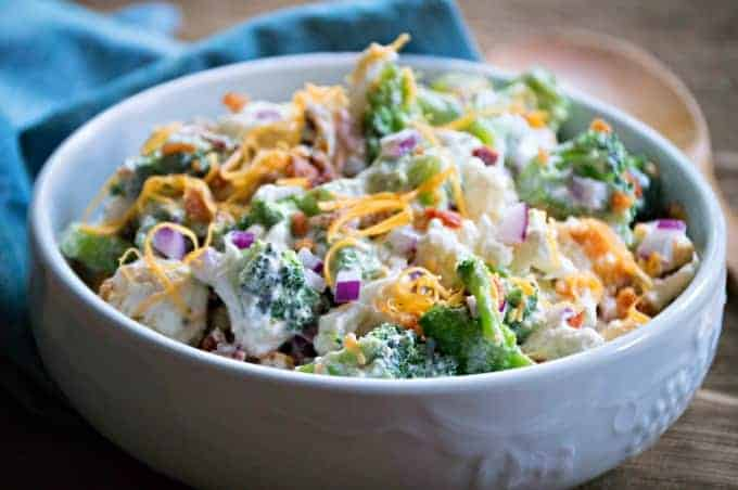 Broccoli, Cauliflower and Bacon Salad topped with shredded cheese