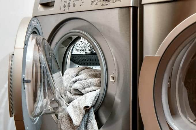 How to Get Rid of Mildew Smells in the Laundry - Towel hanging out of front-loading washer