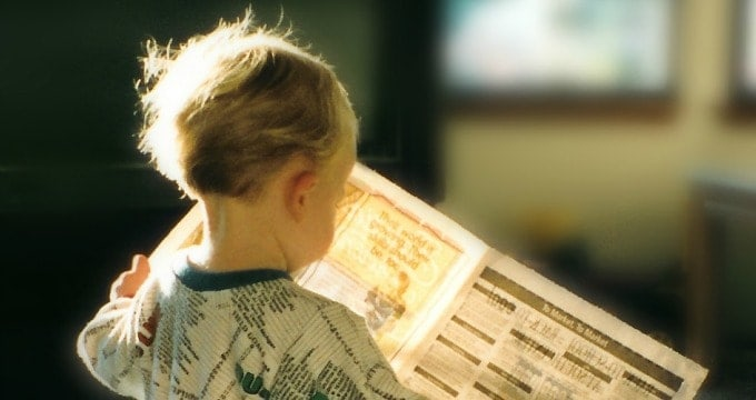 Toddler reading a newspaper in the morning
