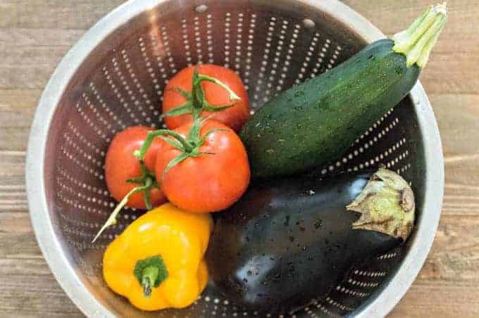 Fresh tomatoes, pepper, zucchini and eggplant in a colander