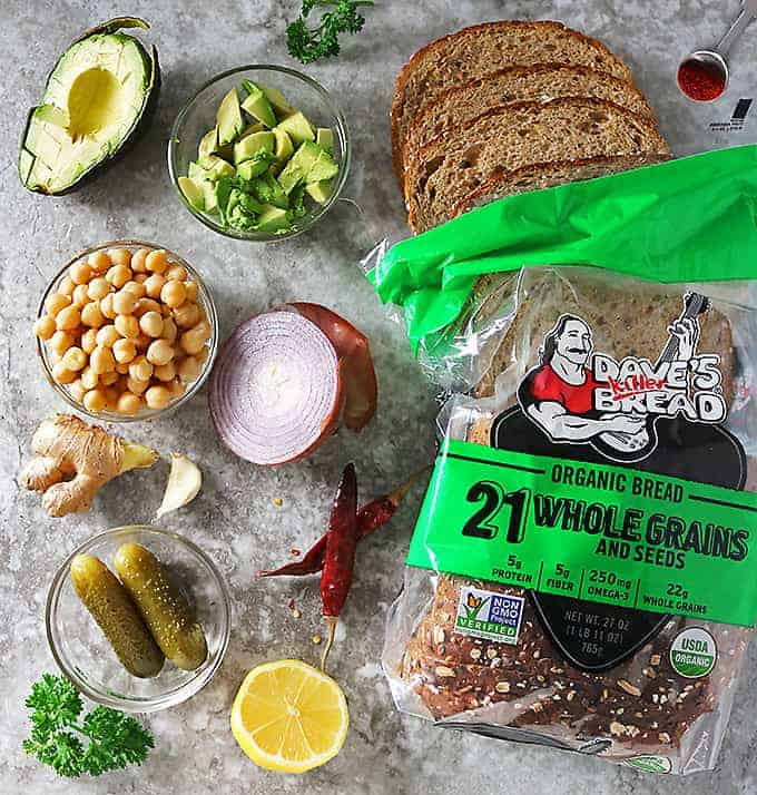 Overhead photo of Dave's Killer Bread and ingredients to make Chickpea Avocado Salad Sandwiches