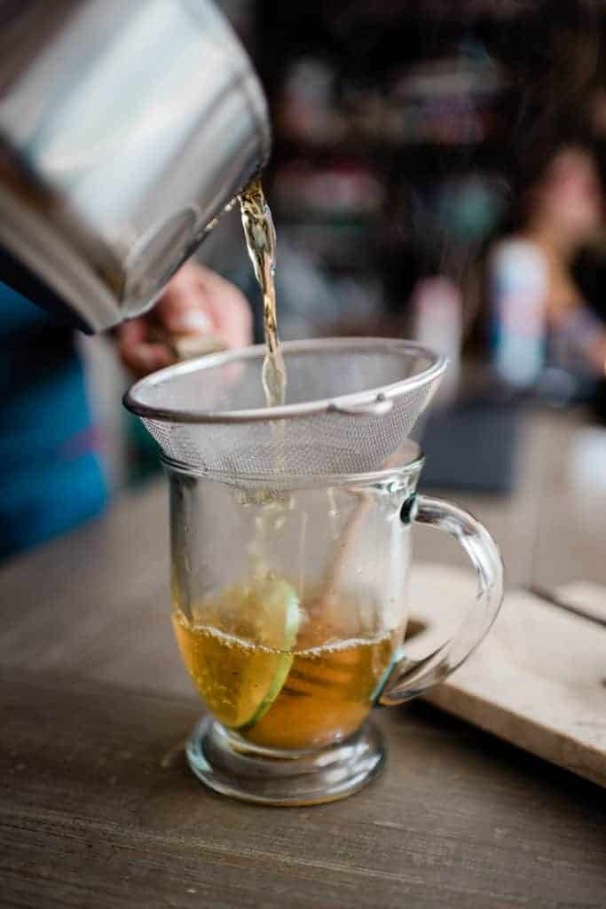 Pouring tea into glass with strainer.