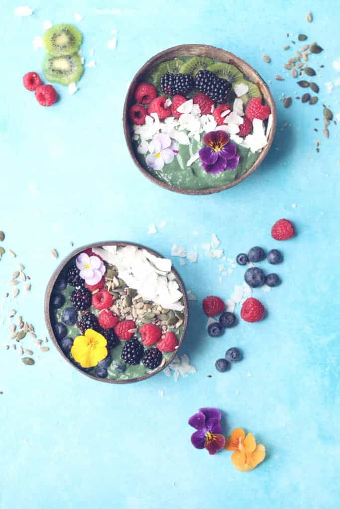 Overhead shot of two green smoothie bowls topped with fresh fruit