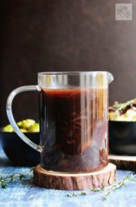 Clear glass full of delicious vegan red wine gravy
