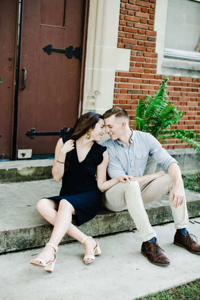 man and woman sitting on the stairs touching each others backs and almost kissing, engagement session pictures,