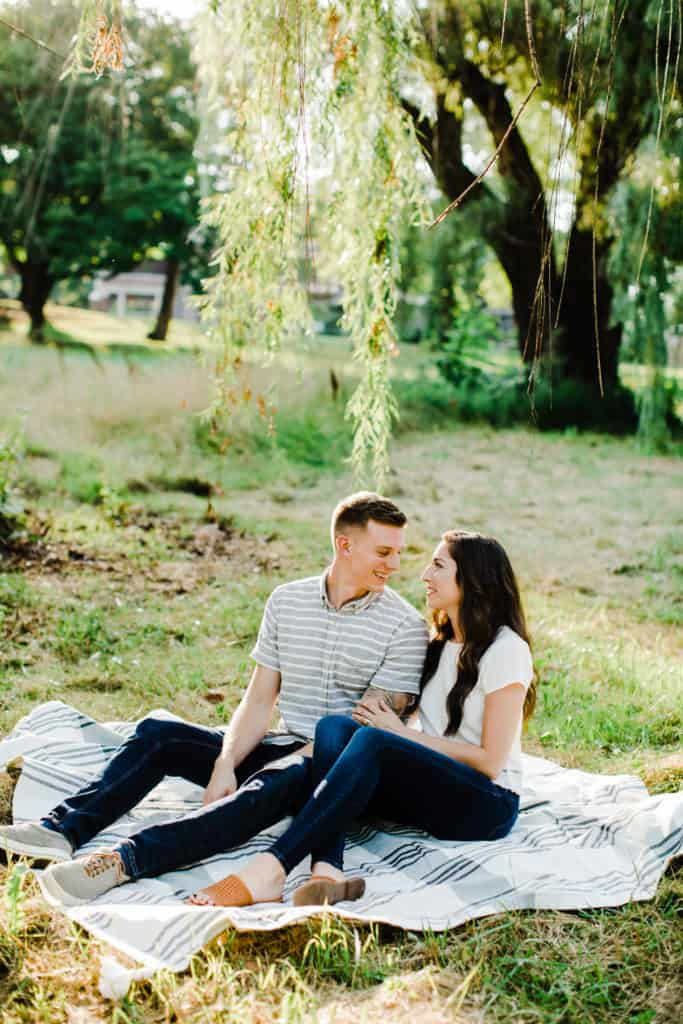 couple sitting golden hour engagement pictures