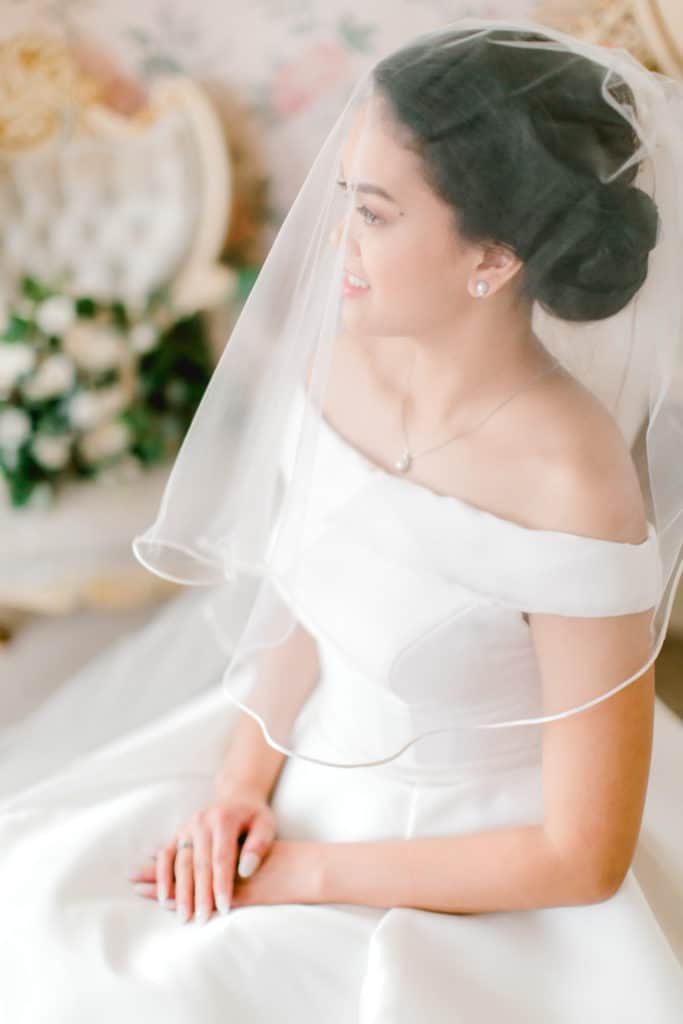 bride sitting on the chair looking away from the camera, in the background wedding bouquet on the white chair